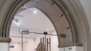 Арочный проем с цельностеклянной дверной конструкцией